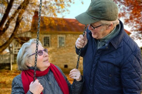 happy-senior-couple-on-swing-in-garden